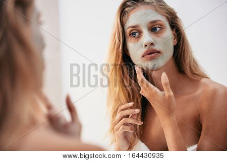 Woman looking in the mirror with mask on her face. Female applying facial cosmetic mask in bathroom.
