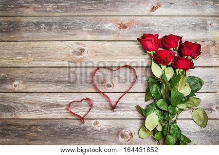 bouquet of red roses on wood background with hearts from ribbon. Valentines Day background