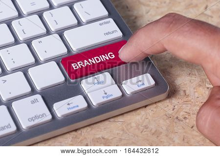 Man pressed keyboard button with branding word