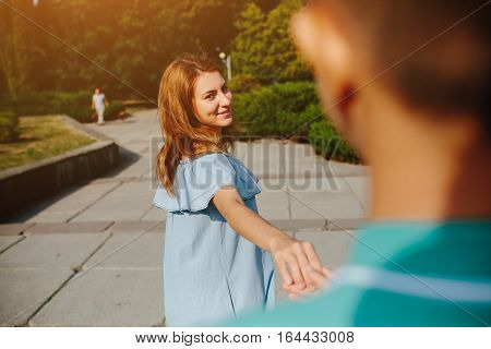 Young woman leading her lover by hand in park, looking at him, playfully laughing