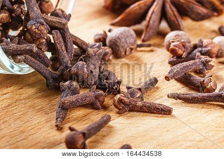 cloves, allspice, star anise on a wooden board