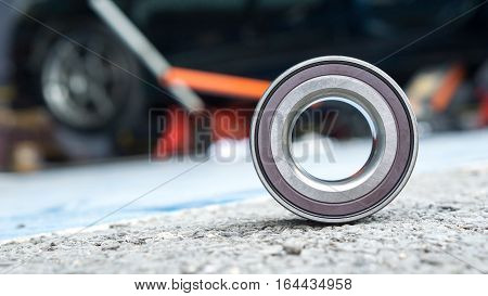 Car Suspension and car bearing parts concept - New wheels car bearing on asphalt floor in garage and copyspace