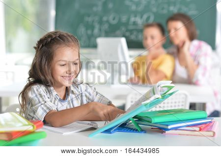children at school sit in the classroom with teacher
