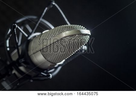 Microphone and audio console in holder, isolated on dark background in recording studio