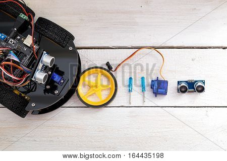 robot on four wheels wheel screwdrivers and servo on a wooden white table. View from above