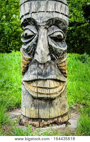 Wooden carving face on totem pole Indian Museum Poland.