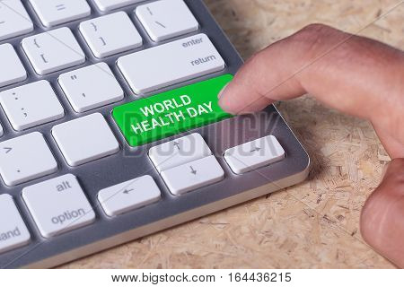 Man pressed keyboard button with World Health Day word