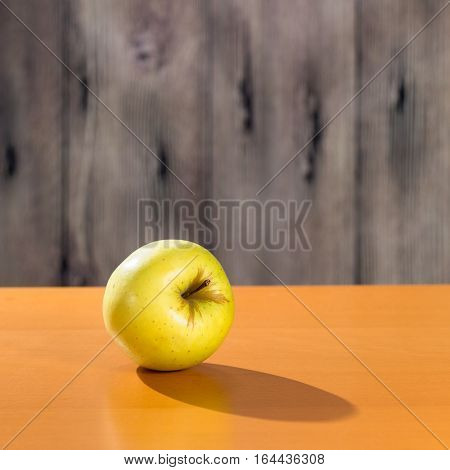 One yellow apple on the orange table. Copy space