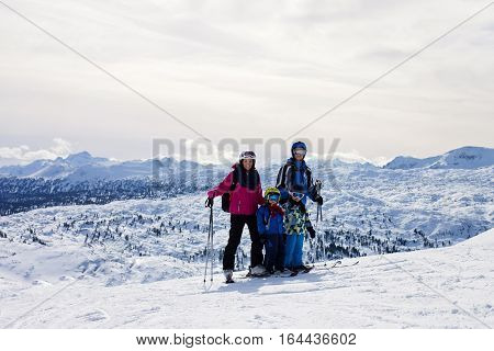 Young happy family with two childrens boy brothers skiing in Austrian ski resort on a sunny winter day