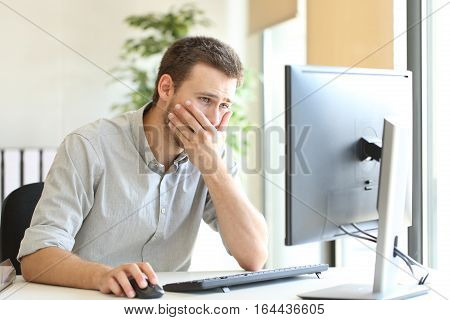 Worried businessman working trying to solve troubles on line with a desktop computer at office