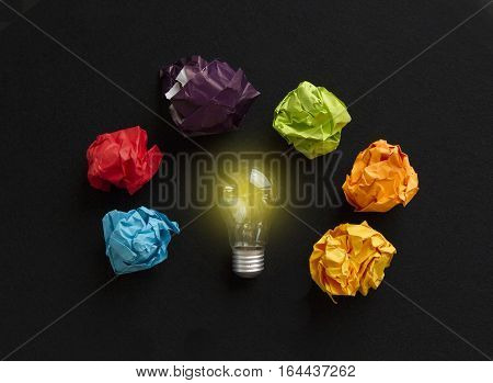 Idea conceot with bulb and different colors paper wads on black background
