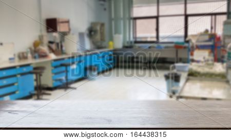 Laboratory interior template for a poster webpage leaflet or powerpoint presentation (blur image) with selected focus empty wood table for display your product