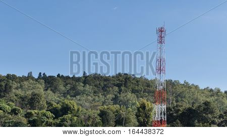 telephone tole elecommunication tower with forest mountain and blue sky