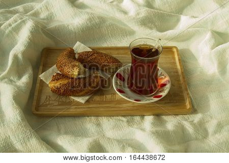 Bagel and cup of turkish tea on the wood tray with Istanbul picture on the bedcover breakfast in bed