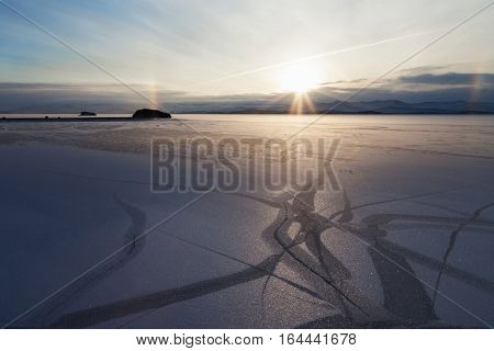 Landscape with natural drawing on snowed icefield and solar halo in the background