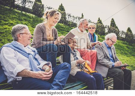 Group of senior people with some diseases walking outdoors - Mature group of friends spending time together