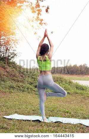 Young Woman Practicing Yoga Exercises Outdoor In Park,  Relax In Nature
