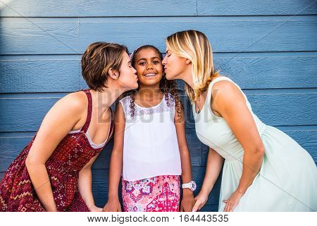 Lesbians mothers with adopted child - Happy homosexual family playing with her daughter