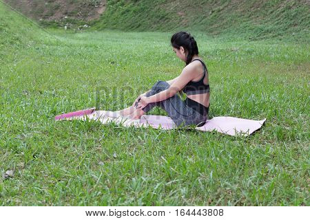 Young Woman Sitting On Mat After Exercises Outdoor In Park,  Relax In Nature
