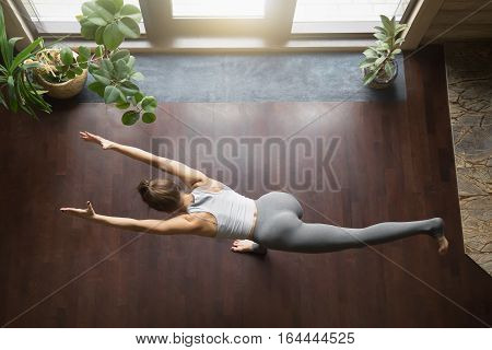 Beautiful young model working out in home interior, doing yoga exercise on wooden floor, standing in warrior III, virabhadrasana 3, balancing stick pose, tuladandasana. Top view. Full length