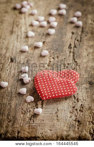 Two red hearts with heart shaped candies on wooden background, valentine's day concept