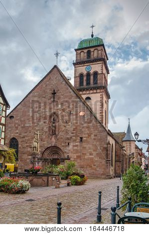 Medieval church in Kaysersberg with fountain in front of her Alsace France