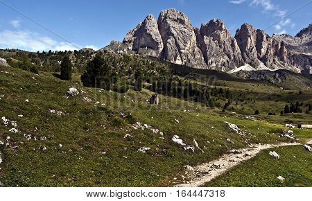 hiking trail with meadow panorama of Odle mountain ridge with sharp Grosse Fermeda peak and nice sky with only few clouds above Val Gardena valley in Dolomites