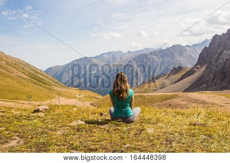 Woman are sitting in yoga style and looking into the distance at the mountains Tien Shan mountains near Shymbulak ski resort Almaty Kazakhstan 2016