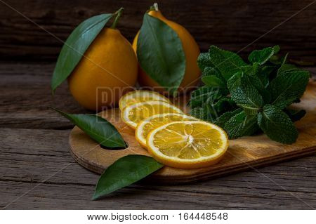 Fresh Mint And Lemon Slices On Wooden Board