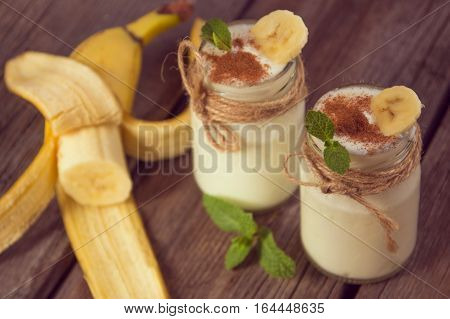Organic homemade sweet milk dessert with banana cinnamon and mint on the wooden background