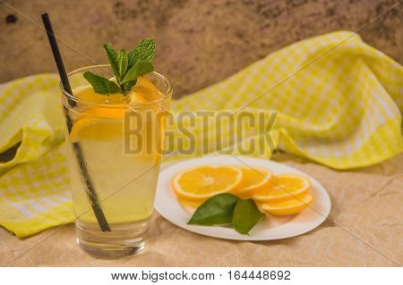 Fresh lemonade in glass with mint and ice on the table
