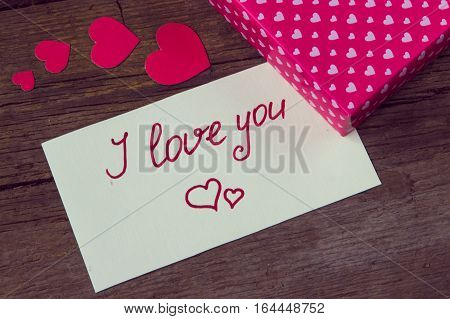 I love you handwritten on white paper and hearted gift box on wooden