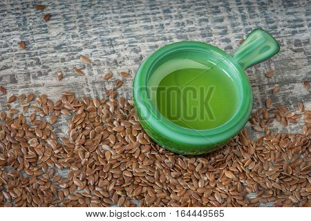 Flax seeds and linseed oil on a wooden board