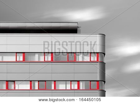 Abstract looking black and white modern building with red windows