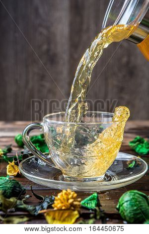 Herbal tea is poured into cup from kettle and table with decorations of dried flowers
