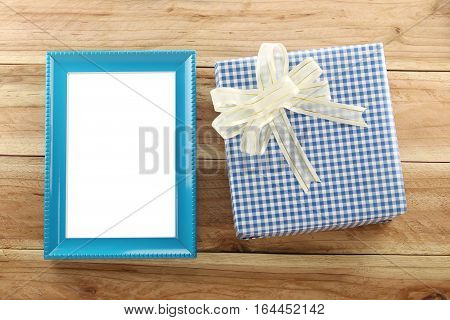 Blue gift box place near blue wooden frame on the wood floor in concept of Christmas and New year.