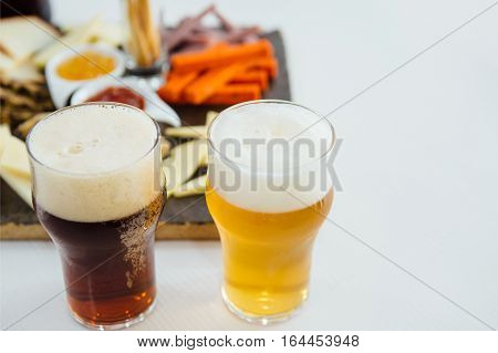 Glasses of fresh light and dark craft beer with froth and snack board