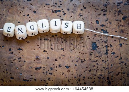 English Text On A Wooden Cubes Strung On A Thread On A Brown Cork Background, Copy Space