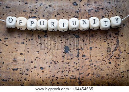 Opportunity Text On A Wooden Cubes Strung On A Thread On A Brown Cork Background