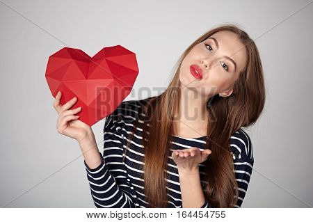 Beautiful smiling woman with red lips holding red polygonal paper heart shape blowing a kiss at camera