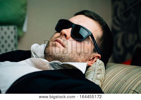 Business man in sunglasses is resting on the couch