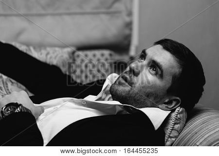 Business man is resting on the couch. Black and white photography