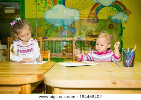 Two little kids drawing with colorful pencils at the table in Montessori preschool class. Little girls sisters in kindergarten