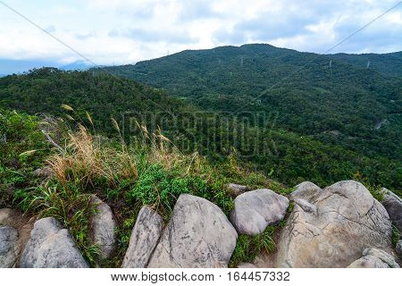 Diverse Taiwan landscape of huge rocks, tall grass, low hills, and forested mountains along the Jin Mian trail in Neihu