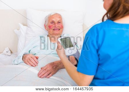 Caretaker Measuring Blood Pressure