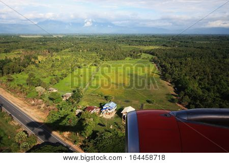View from an airplane looking down to the green forest with its own shadow below