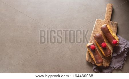 Traditional French Dessert. Eclair With Chocolate Icing And Rasp