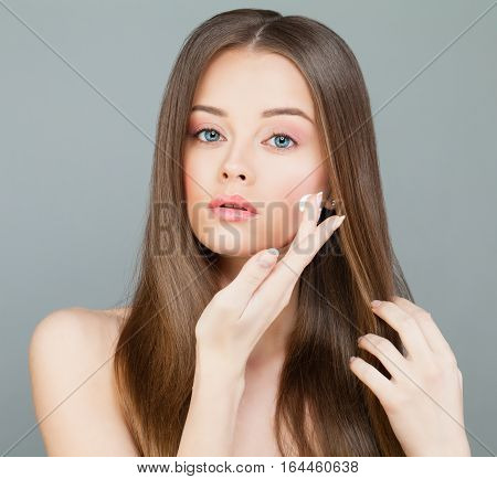 Young Woman Spa Model Applies a Moisturizer to her Face. Skincare Concept woman, apply, cream, moisturizing, moisturizer, spa, face, healthy, model, care, skincare, health, brown, skin, long, hair, routine, wellbeing, purity, wellness, young, white, beaut