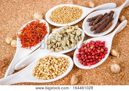 Spices on a white spoon on wooden background.