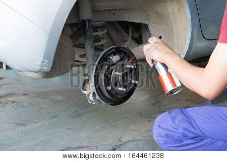 Mechanic Spray Chemical To Clean Brake